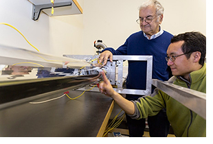 Professor Roland Winston (standing) and postdoctoral researcher Lun Jiang work on a solar collector system.